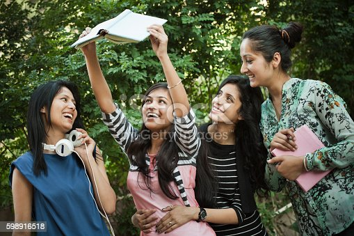 istock Group of girl students looking at book with toothy smile. 598916518