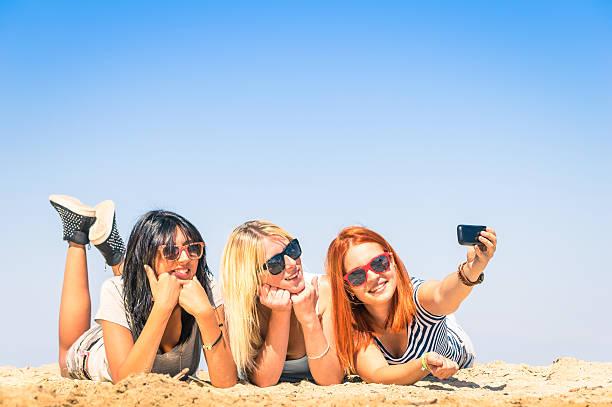 gruppe von freundinnen, die ein selfie am strand - happy weekend bilder stock-fotos und bilder