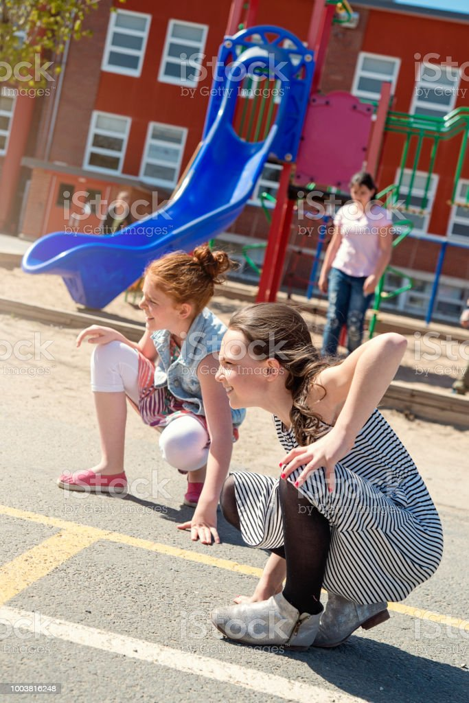Group of girls active in school playground at recess.. stock photo