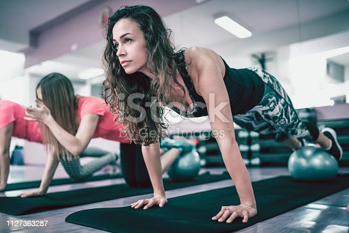 Three fit and handsome girls are doing and planks on the fitness mat at the gym