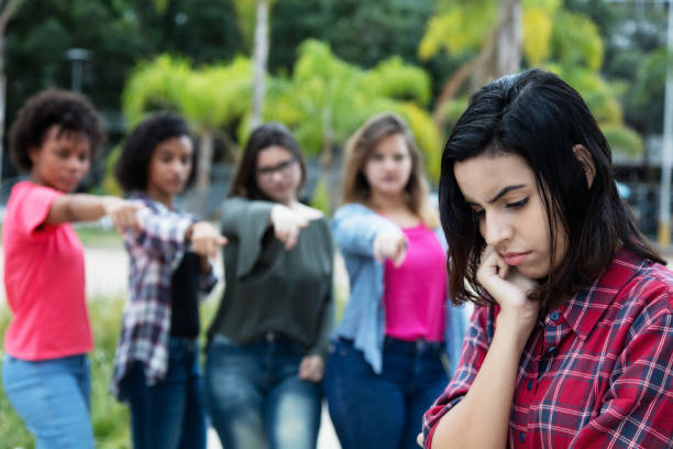 Group of girls bullying an arabic young adult woman Group of girls bullying an arabic young adult woman without friends outdoors critic stock pictures, royalty-free photos & images