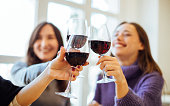 Group of girls (women) drinking red wine, celebrating and having fun together, focus on clinking glasses