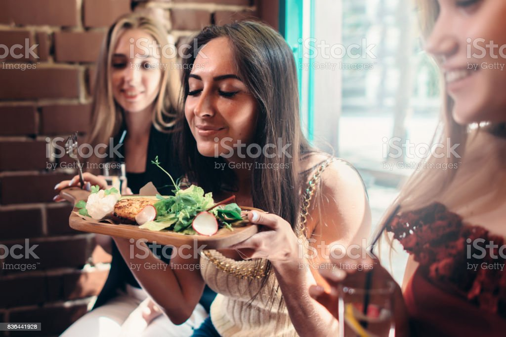 Group of girls having lunch in fashionable restaurant. Smiling young woman enjoying the smell of delicious salad served on wooden plate royalty-free stock photo