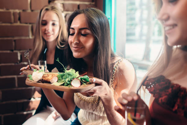 Group of girls having lunch in fashionable restaurant. Smiling young woman enjoying the smell of delicious salad served on wooden plate stock photo