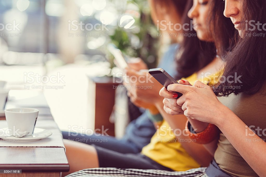 Group of girls in a cafe texting on smartphones stock photo