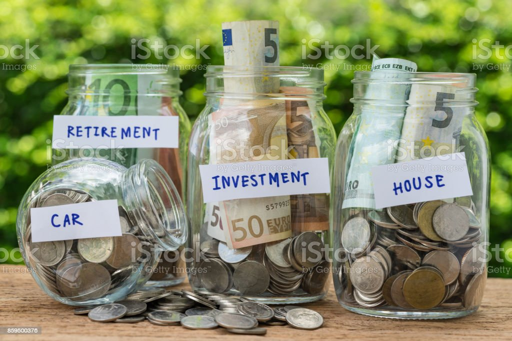 group of glass jar bottles with full of coins and banknotes labeled as investment, house, car and retirement as savings or investment concept stock photo