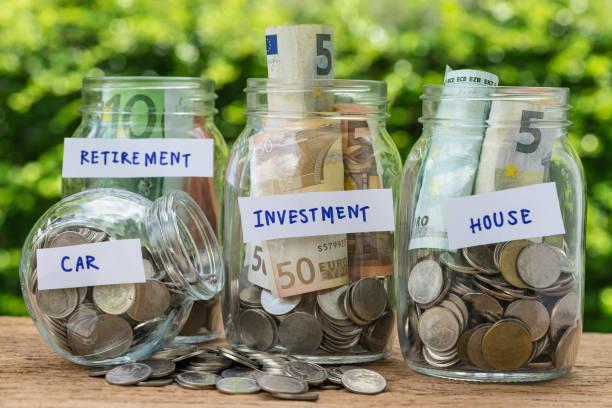 Groupe des bouteilles de bocal en verre avec plein de pièces de monnaie et billets marqués comme investissement, maison, voiture et retraite en tant que concept d'épargne ou d'investissement - Photo