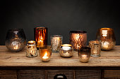 A group of glass tea light holders and glowing candles, shot on a wooden table, with a dark grey background