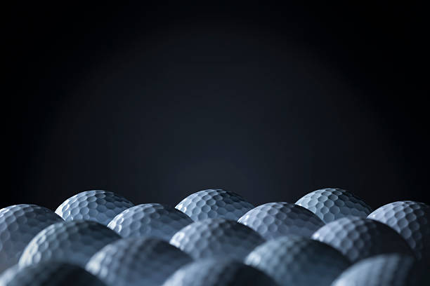 Group of golf balls isolated on black background. stock photo