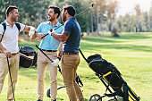 Multi-ethnic group of male golf players talking on the course playground