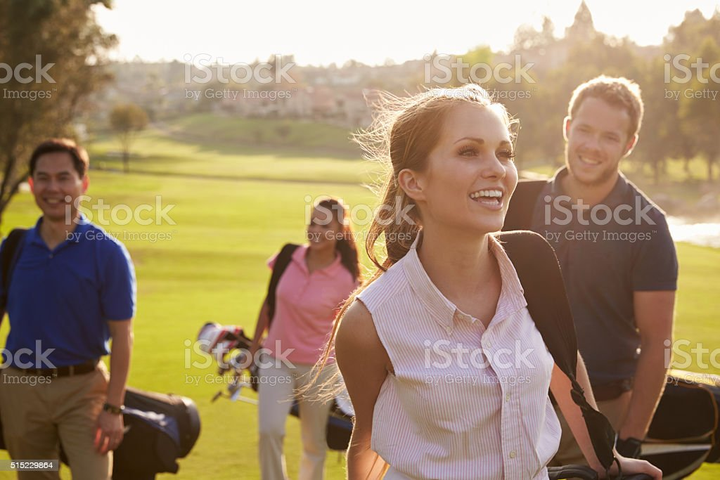 Group Of Golfers Walking Along Fairway Carrying Golf Bags stock photo