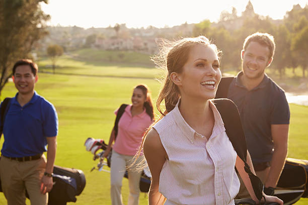 group of golfers walking along fairway carrying golf bags - female golfer stock photos and pictures