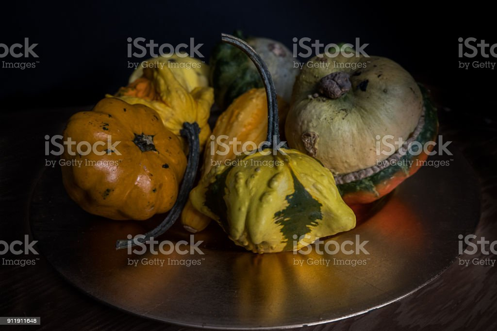 Group of gourds on a reflective plate stock photo