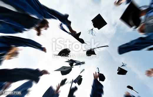1009462356 istock photo Group of graduate students throwing graduation hats to the sky 1156917135