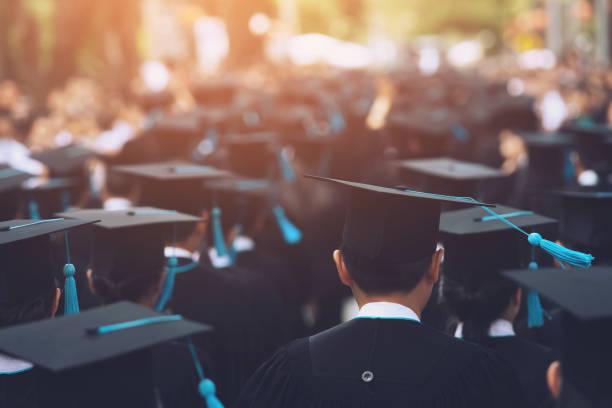 groupe de diplômés au cours de l'entrée en vigueur. félicitation du concept l'éducation à l'université. remise des diplômes, a félicité les diplômés de l'université au cours de l'entrée en vigueur. - remise de diplôme photos et images de collection