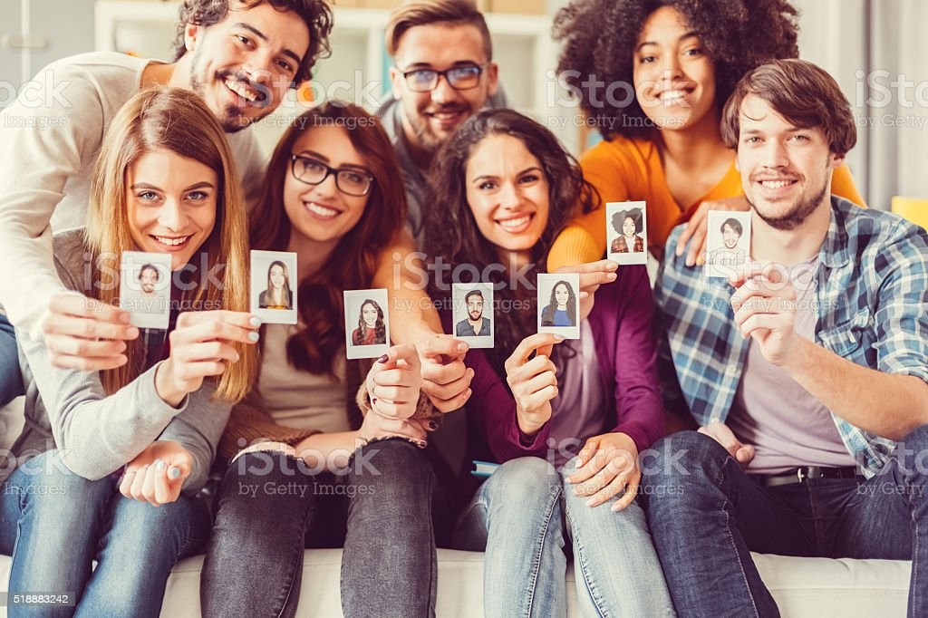 Group of graduates showing instant self portraits stock photo