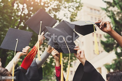 istock A group of graduates throwing graduation caps in the air 947295034