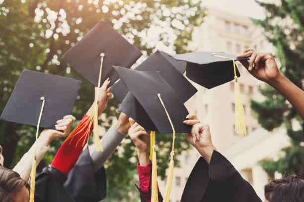 un grupo de graduados lanzan casquillos de la graduación en el aire - graduación fotografías e imágenes de stock