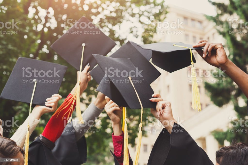 A group of graduates throwing graduation caps in the air stock photo