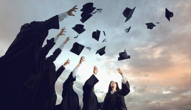 A group of graduates throws hats up into the sky. A group of graduates throws hats up into the sky.Graduation.University gesture and people concept. alumnus stock pictures, royalty-free photos & images