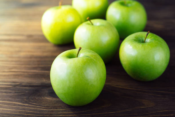 Group of green apples on brown wooden background. Group of green apples on brown wooden background. Close up granny smith apple stock pictures, royalty-free photos & images