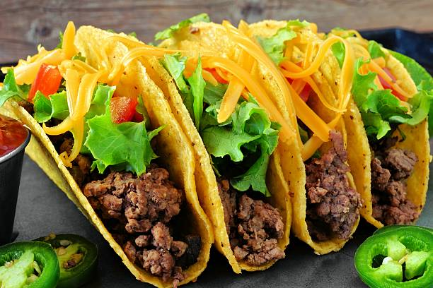 Group of ground beef hard shelled tacos close up Group of hard shelled tacos with ground beef, lettuce, tomatoes and cheese close up taco stock pictures, royalty-free photos & images