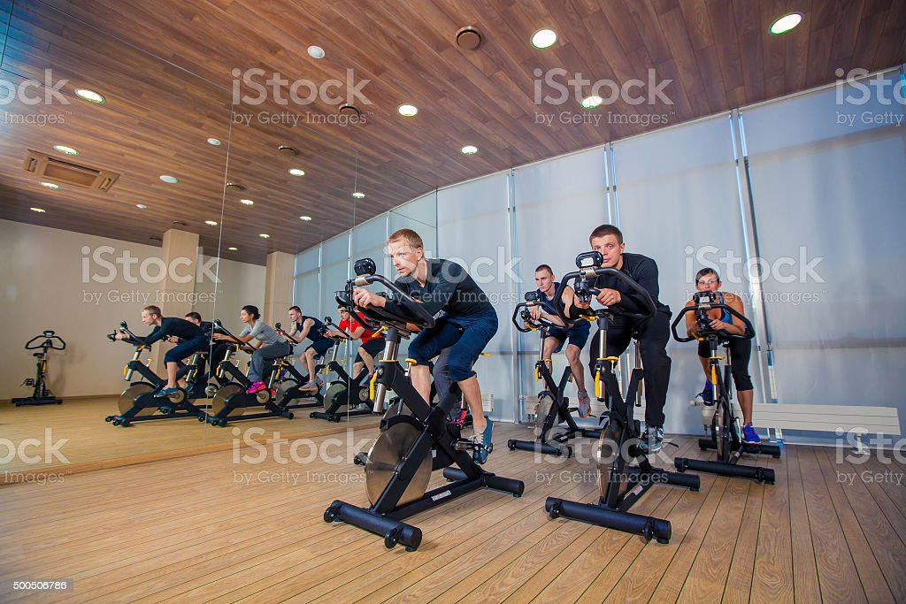 Group of gym people on machines, cycling In Class stok fotoğrafı