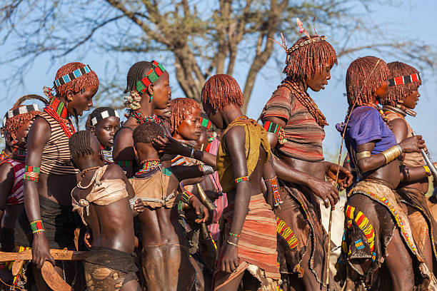 group of hamar women dance at bull jumping ceremony. - horn of africa stock photos and pictures
