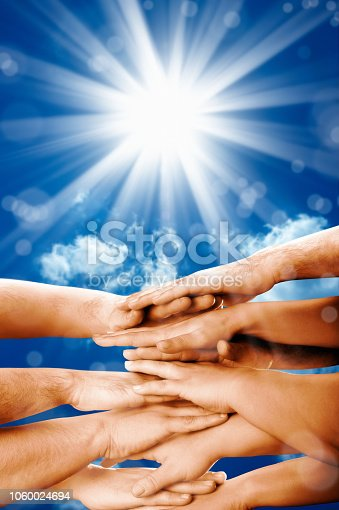 1016771914 istock photo group of hands clasped together over blue sky with light beam 1060024694
