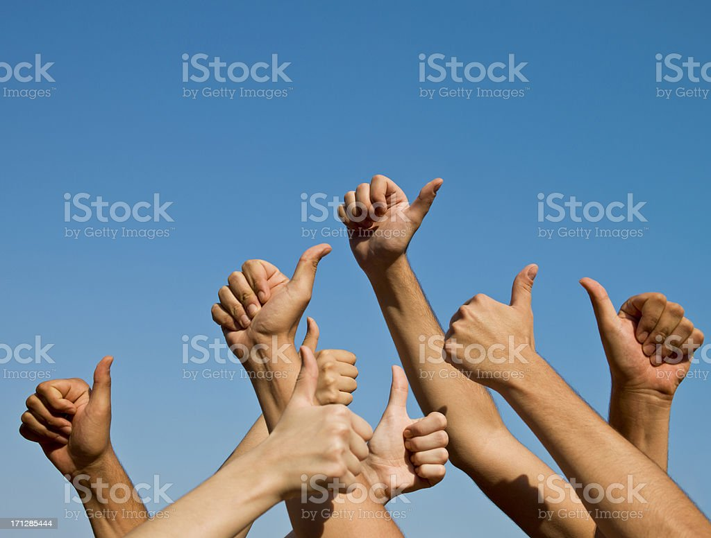 Group of hands giving thumbs up over blue sky royalty-free stock photo