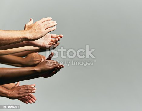 istock Group of hands held out, applauding, against grey background 912886074