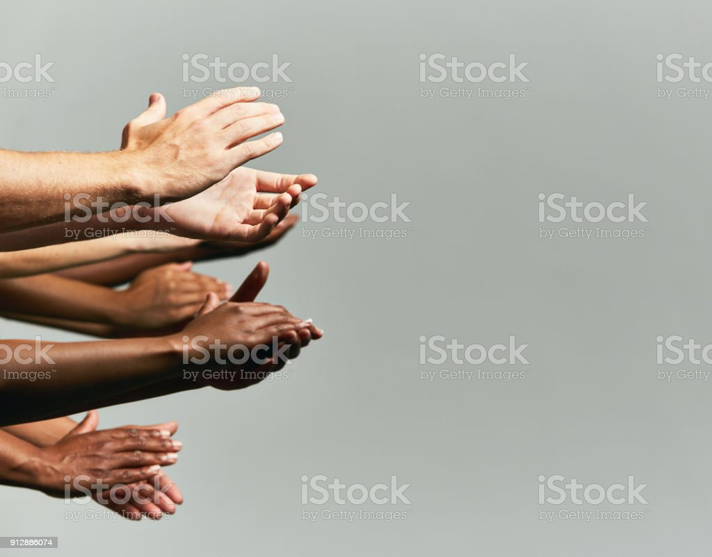 Group of hands held out, applauding, against grey background stock photo