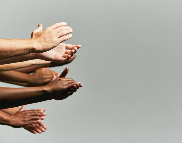 group of hands held out, applauding, against grey background - спасибо стоковые фото и изображения