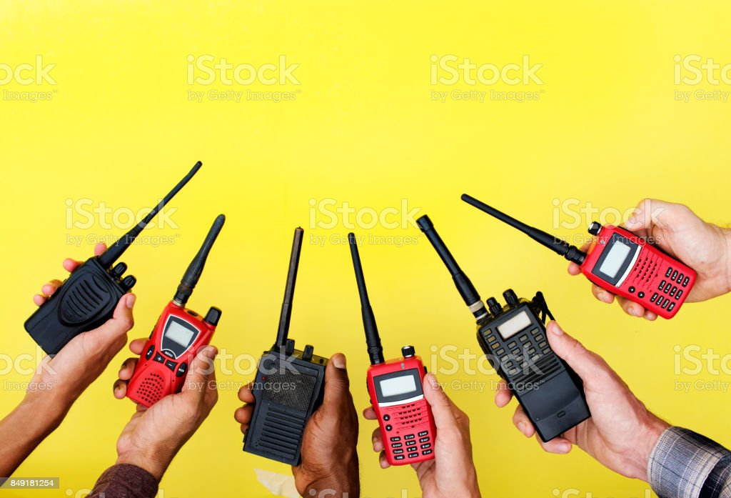 Group of hands holding portable two way radios with yellow background stock photo