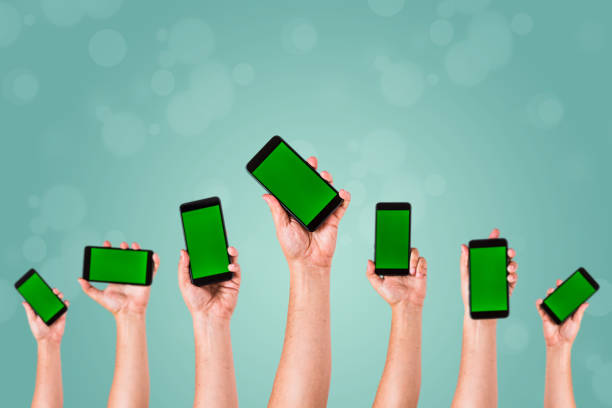 group of hands Raising up Smart phones against green background - Hands holding phones stock photo