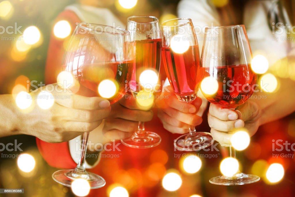 Grupo de mãos brindando os copos de vinho tinto para Natal ou celebrando a festa de Natal. Closeup fotografia com bokeh luz para feriado de ano novo - foto de acervo