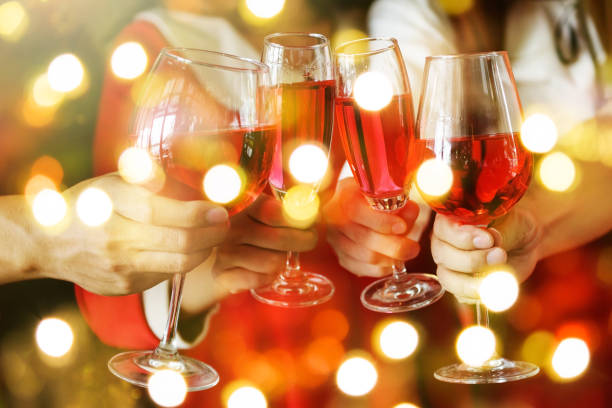 group of hands toasting glasses of red wine for christmas or xmas celebrating party. closeup photo with bokeh light for new year holiday - holiday event stock pictures, royalty-free photos & images