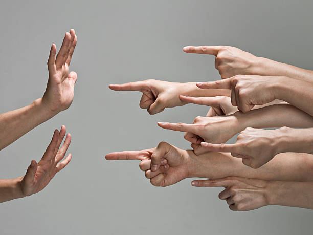 Group of hands with pointing finger Multiple white hands are pointing index fingers from the right to the left at one set of hands.  The pair of hands that are being pointed at are up in a defensive pose, with fingers to the sky and palms towards the pointing fingers. guilty stock pictures, royalty-free photos & images