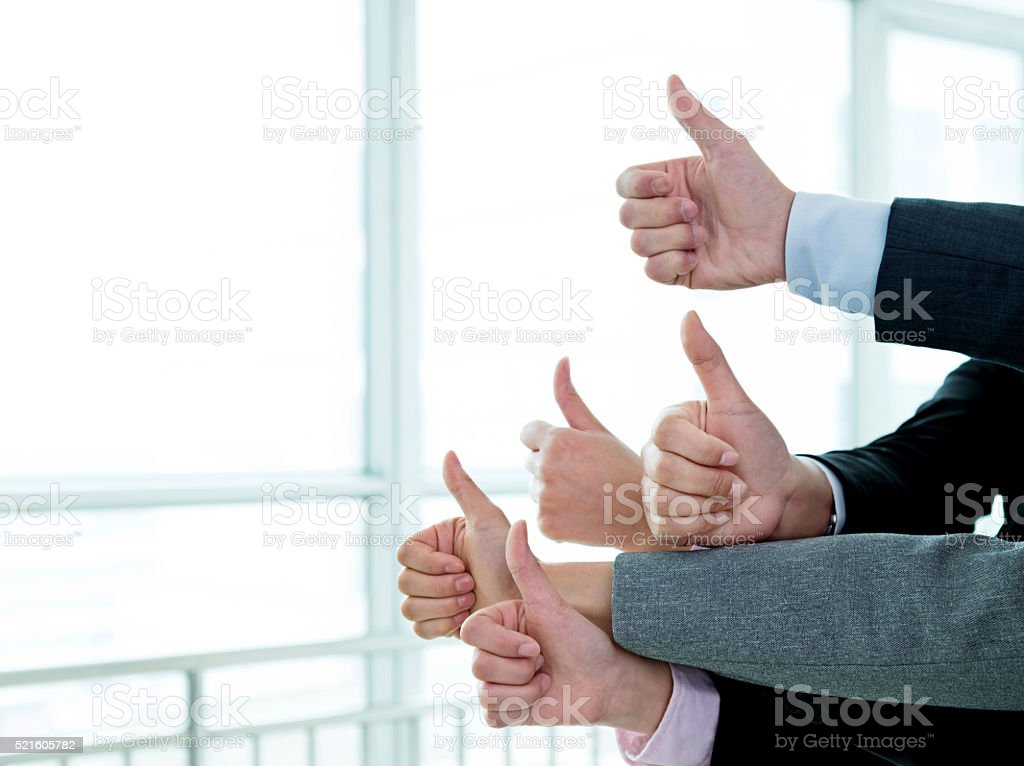 Group of hands with thumbs up in office room.
