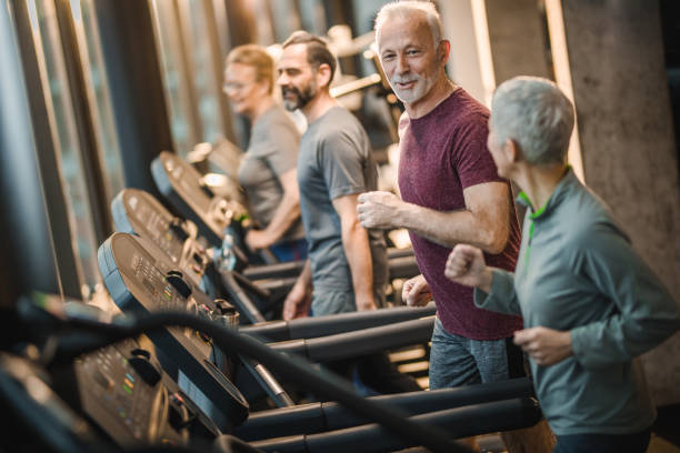 Group of happy active seniors talking while jogging on treadmills in a gym. - foto stock