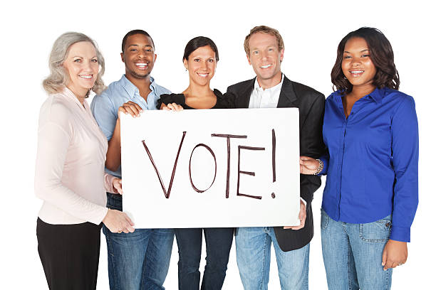group of happy adults holding a vote sign - vote sign stock photos and pictures