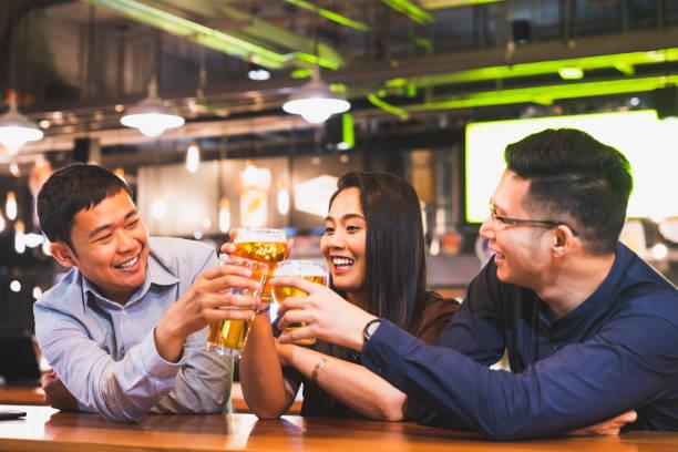 一群快樂的亞洲朋友或辦公室同事在酒吧餐廳或夜總會一起慶祝土司啤酒品脫。工作聚會後, 團隊成功事件或現代友誼生活方式概念 - 日本人 個照片及圖片檔