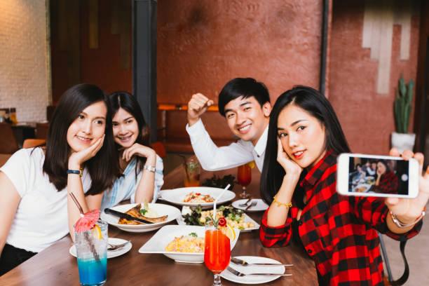 Gruppe von Happy asiatische männliche und weibliche Freunde Selfie fotografieren und mit einem sozialen Toast zusammen im Restaurant. – Foto