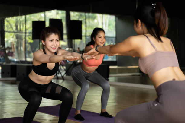 Group of happy Asian women doing squat exercises on yoga mats in aerobics class. Young sporty people smiling while working out in gym studio. stock photo