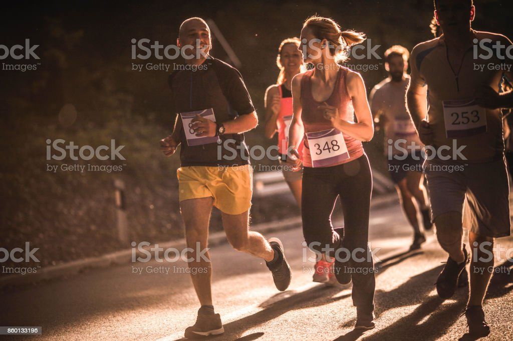 Group of happy athletes having a road running race in nature. stock photo