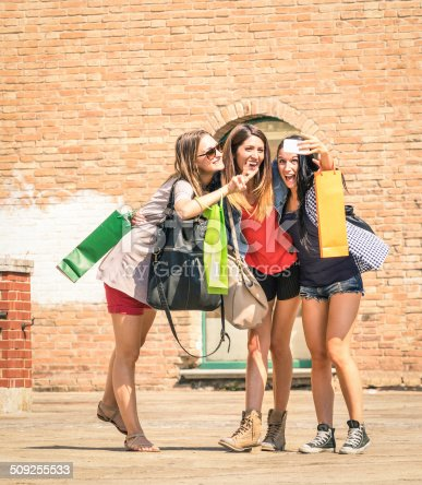 istock Group of happy best friends with shopping bags taking selfie 509255533