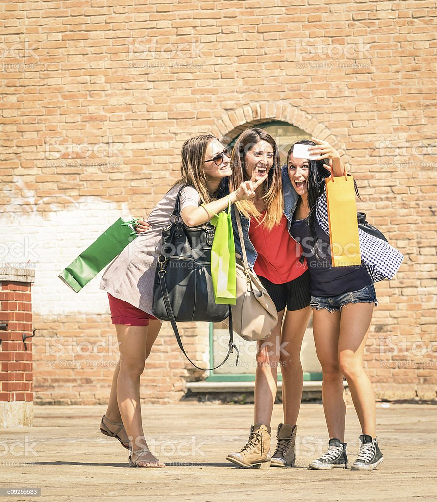 Group of happy best friends with shopping bags taking selfie stock photo