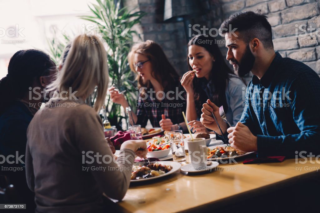 Group of happy business people eating together in restaurant stock photo