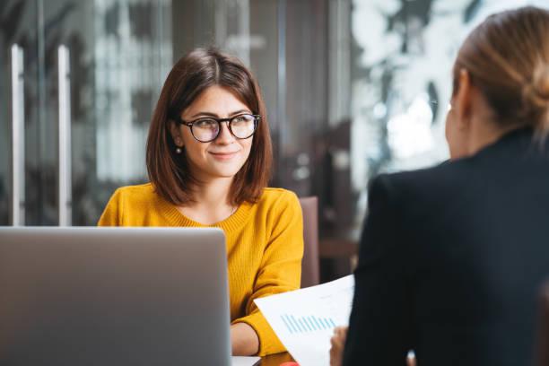 Gruppe glücklicher Geschäftsleute trifft sich am Arbeitsplatz im Büro. Zwei positive Frauen arbeiten mit modernem Laptop für Arbeitskonzept zusammen – Foto