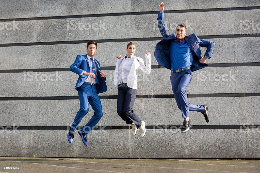 Group of happy business people jumping high up outdoors. stock photo